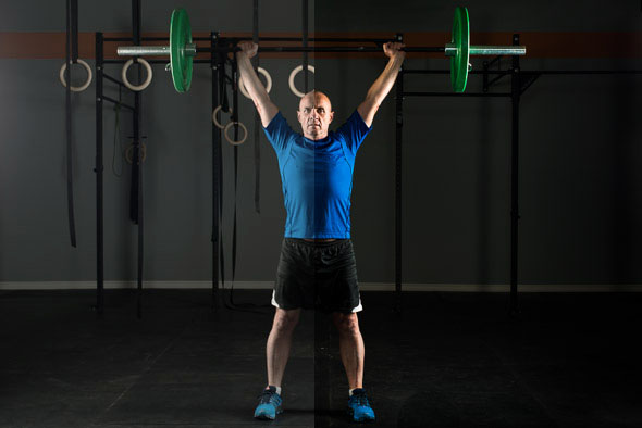 Fit Man Working Out at The Gym Lifting Weights